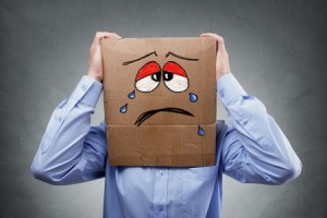 48356011 - businessman with cardboard box on his head showing a crying sad expression concept for headache, depression, sadness, heartache or frustration