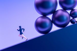 running away from problems, person running down hill chased by large balls
